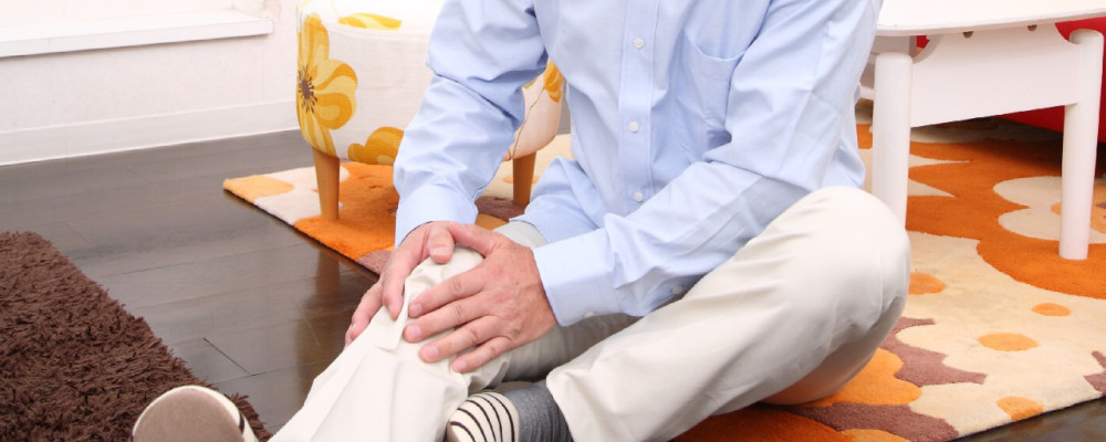 痛む膝を押さえる男性